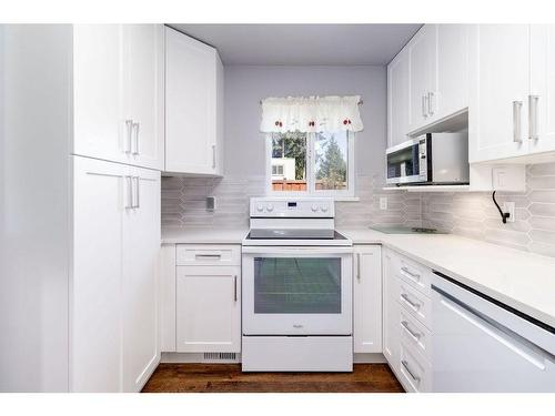 Our new kitchen has white cabinets and grey subway like tiles. All white appliances and natural stone counter tops